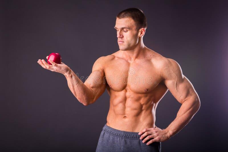 Мышечный парень держа яблоко и грушу стоковая фотография rf