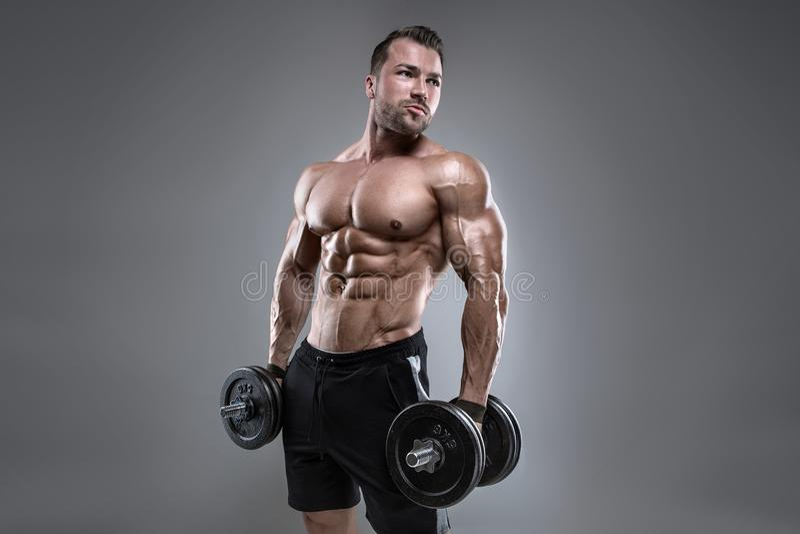 Мышечный парень культуриста делая тренировки с гантелью стоковое фото