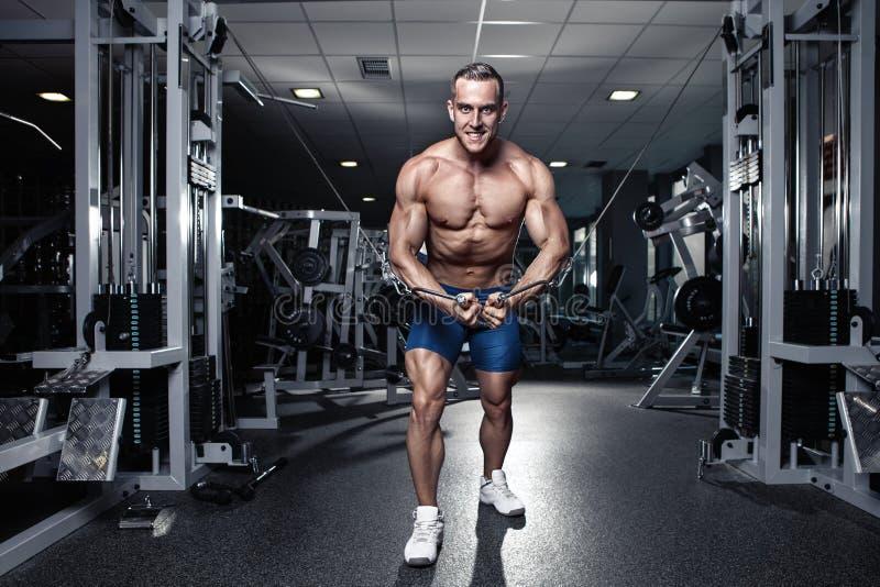 Мышечный парень культуриста делая разминку тренировок в спортзале стоковое фото