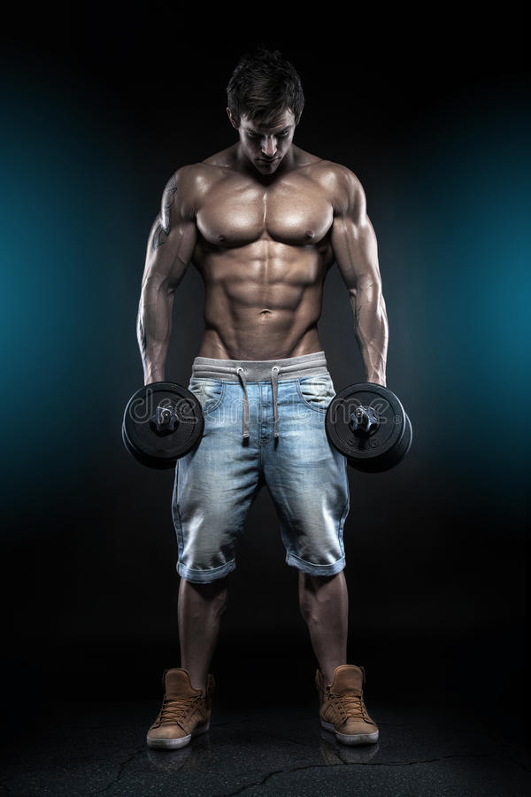 Мышечный парень культуриста делая тренировки с гантелями над bla стоковые фотографии rf