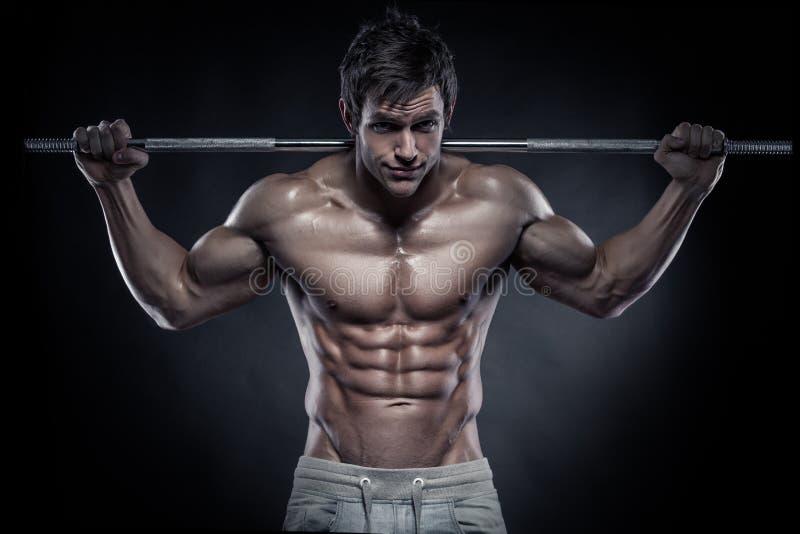 Мышечный парень культуриста делая тренировки с гантелями стоковое изображение