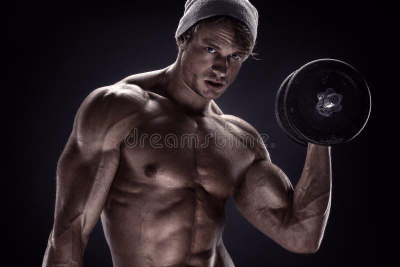 Мышечный парень культуриста делая тренировки с гантелями стоковая фотография