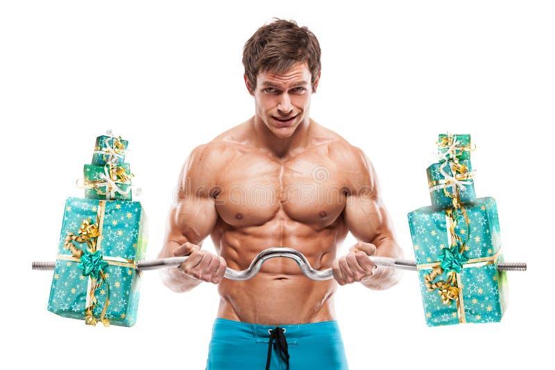 Мышечный парень культуриста делая тренировки с подарками над белым b стоковое фото