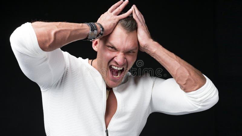 Мышечный парень представляя в студии Гримаса головной боли стоковые изображения rf