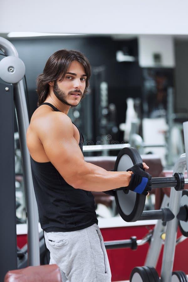 Мышечный человек вытягивая вес металлического стержня стоковое фото rf