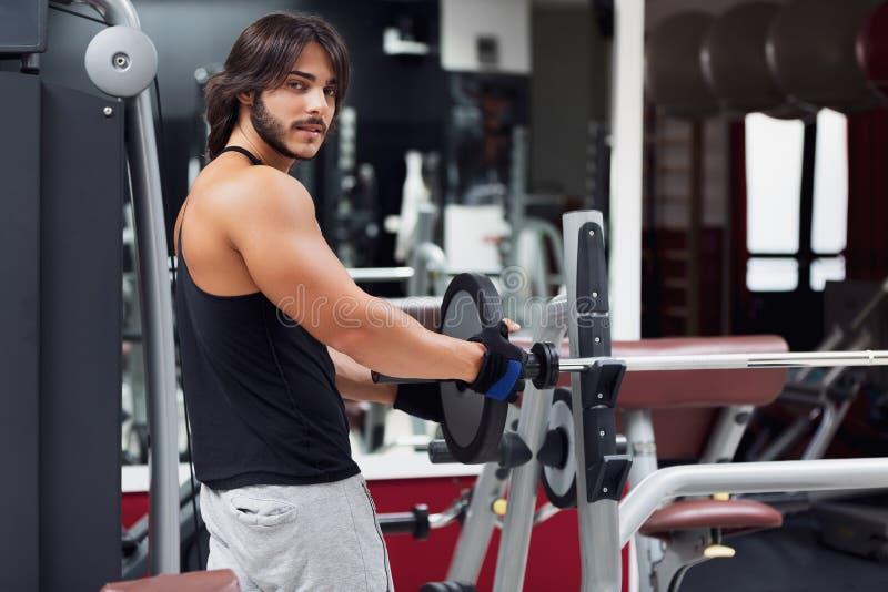 Мышечный человек вытягивая вес металлического стержня стоковые фотографии rf