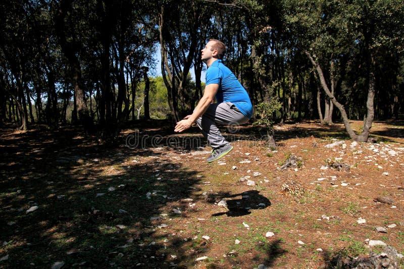 Мышечный человек делая скачку разминки вверх в тренировке воздуха в sportswear красивого спортсмена леса нося скачет вверх в трен стоковые фотографии rf