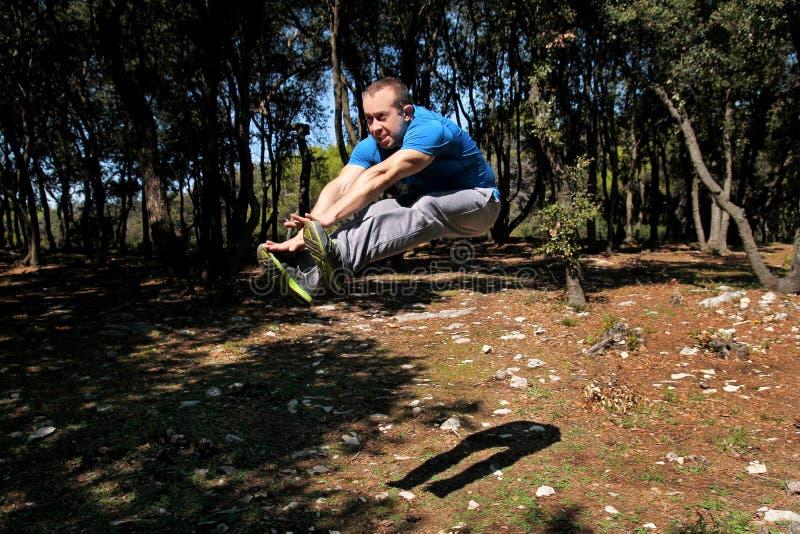 Мышечный человек делая скачку разминки вверх в тренировке воздуха в sportswear красивого спортсмена леса нося скачет вверх в трен стоковое фото