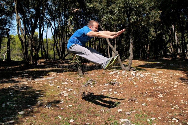 Мышечный человек делая скачку разминки вверх в тренировке воздуха в sportswear красивого спортсмена леса нося скачет вверх в трен стоковая фотография rf
