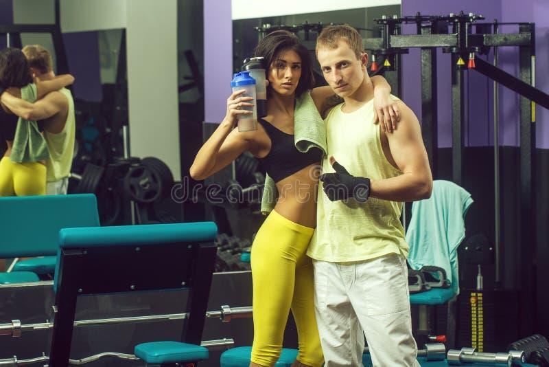 Мышечный человек и сексуальная девушка на тренере спортзала с бутылкой стоковое фото rf