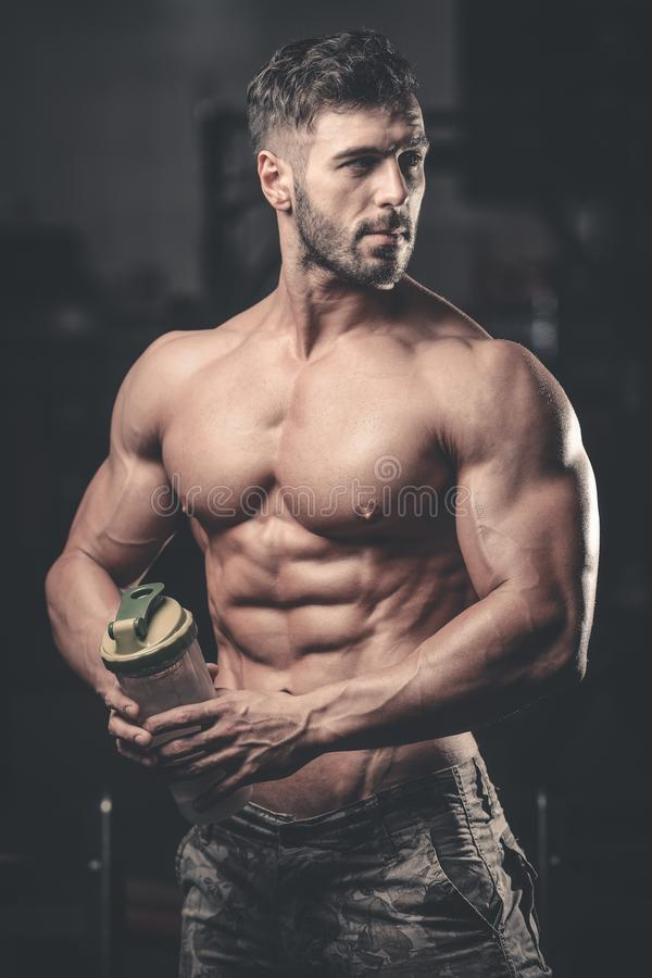 Мышечный человек отдыхая после тренировки и выпивая от шейкера стоковая фотография rf
