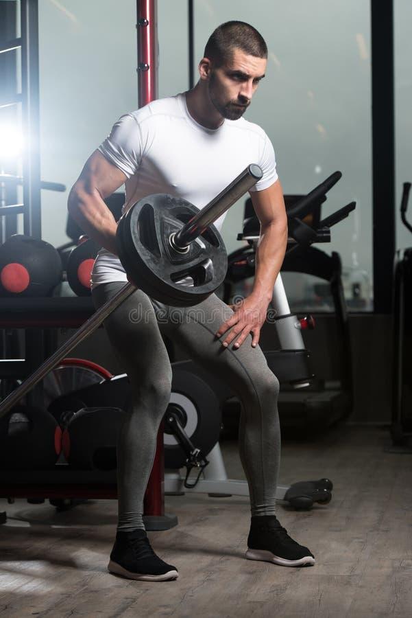 Мышечный человек работая назад с штангой стоковая фотография rf
