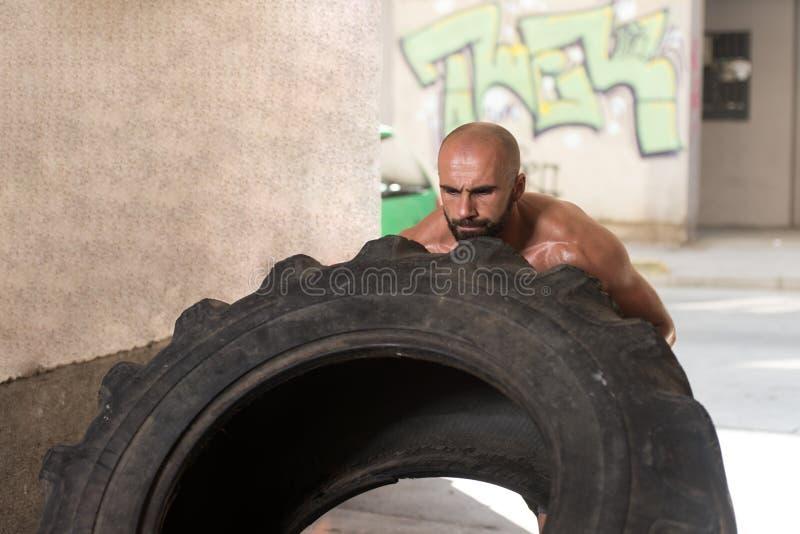 Мышечный человек работая разминку Crossfit сальто автошины стоковое изображение