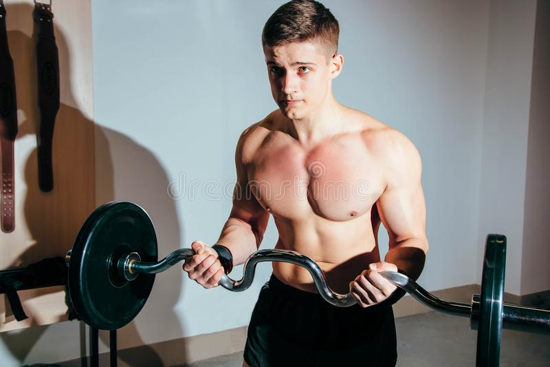 Мышечный человек разрабатывая в спортзале делая тренировки с штангой, сильным мужским нагим abs торса стоковая фотография