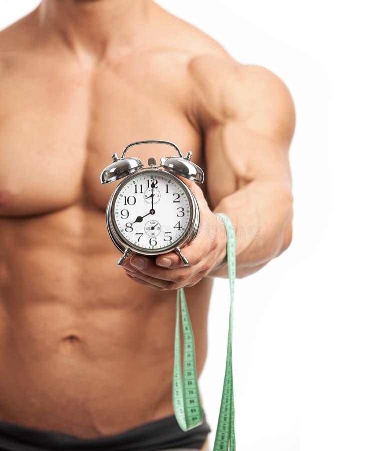Мышечный человек держа часы и измеряя ленту стоковое фото rf