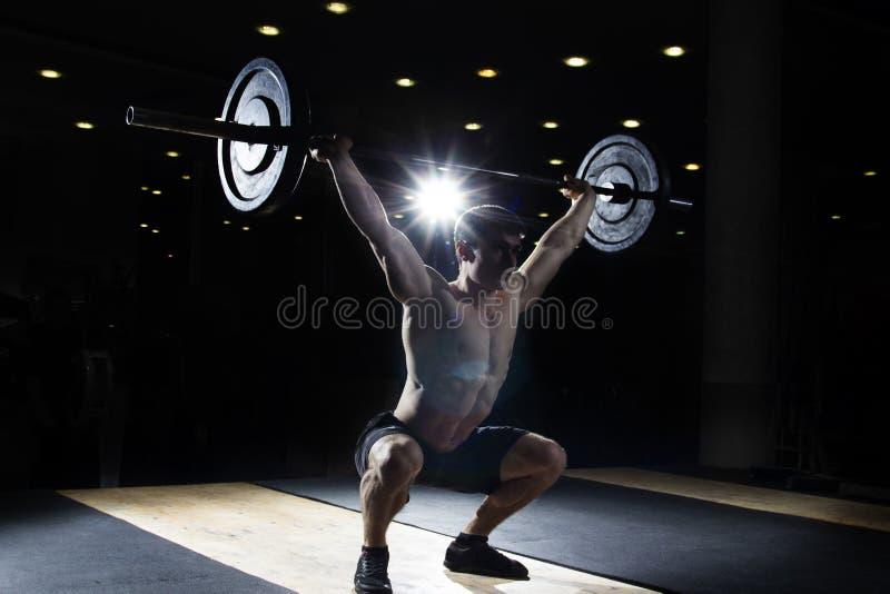 Мышечный человек делая тренировку crossfit в спортзале стоковое изображение