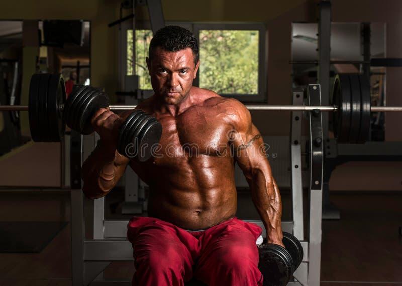 Мышечный человек делая тяжеловесную тренировку для бицепса стоковая фотография rf