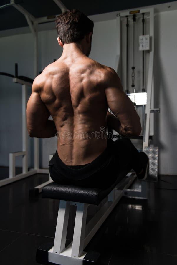 Мышечный человек делая тяжеловесную тренировку для задней части стоковые фото