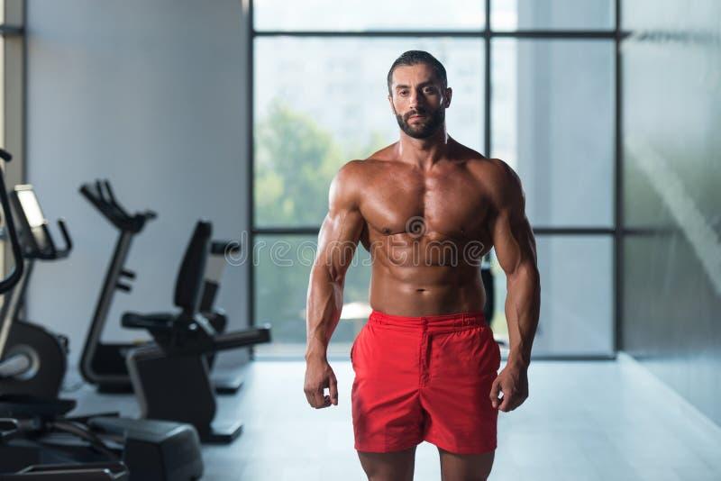 Download Мышечный человек изгибая мышцы в спортзале Стоковое Фото - изображение насчитывающей этничность, мышца: 81815106