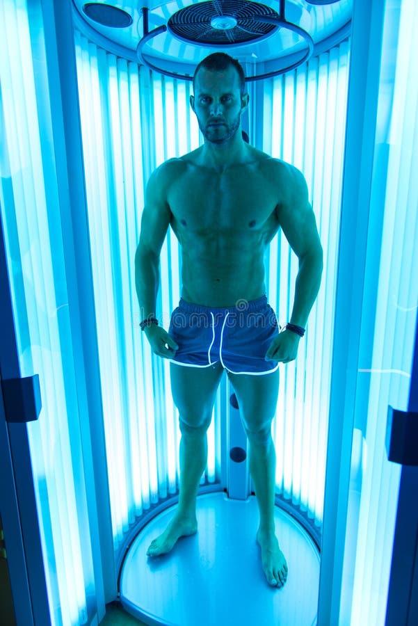 Мышечный человек на солярии в салоне красоты стоковое фото