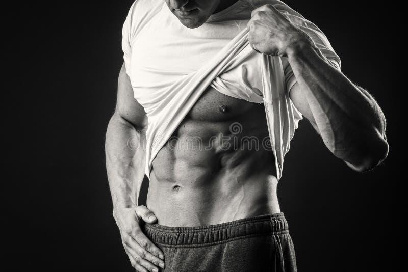 Мышечный человек на темной предпосылке стоковое изображение rf