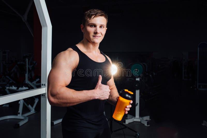 Мышечный человек отдыхая после тренировки и выпивая от шейкера пока показывающ большие пальцы руки вверх стоковые фотографии rf