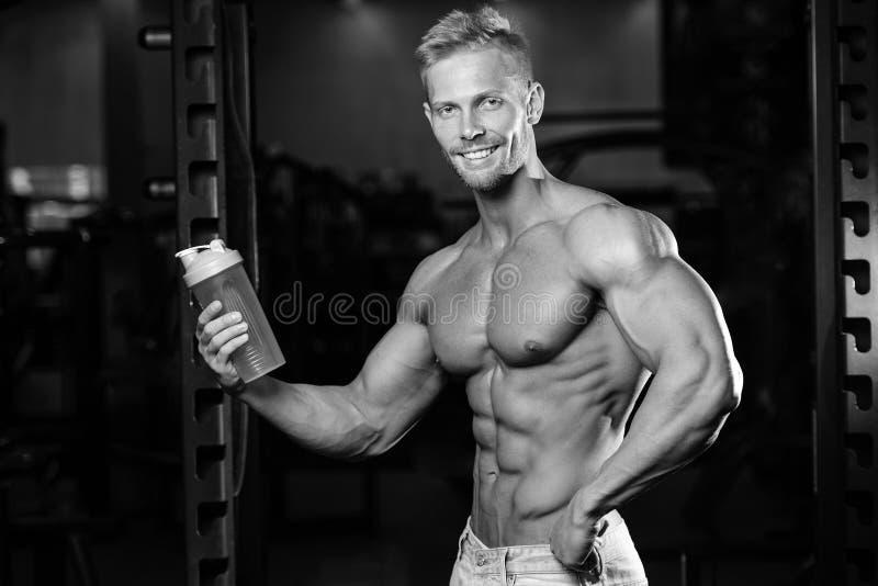 Мышечный человек отдыхая после тренировки и выпивая от шейкера стоковые изображения rf