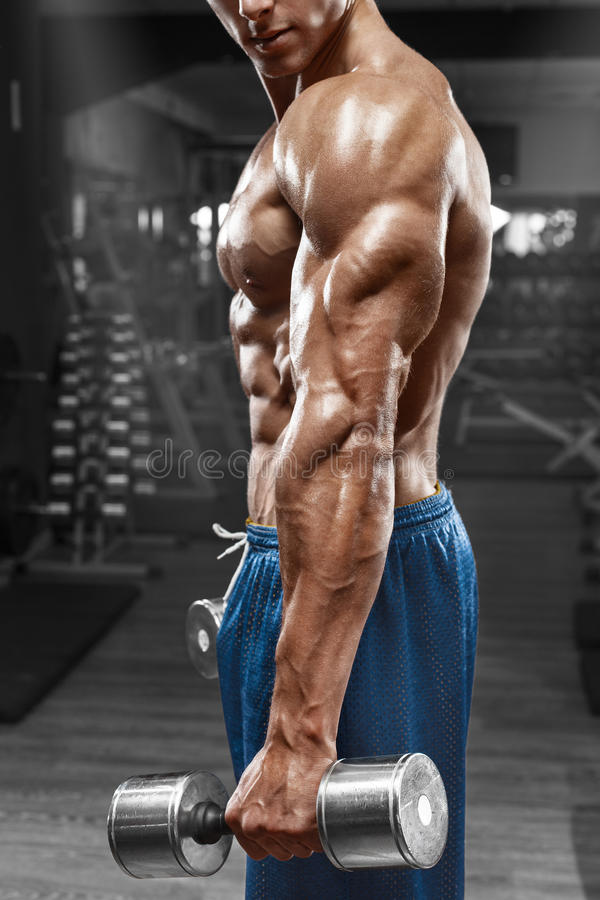 Мышечный человек представляя в спортзале, показывая трицепс Сильные мужские нагие abs торса, разрабатывая, фокусируют на руке стоковое изображение rf