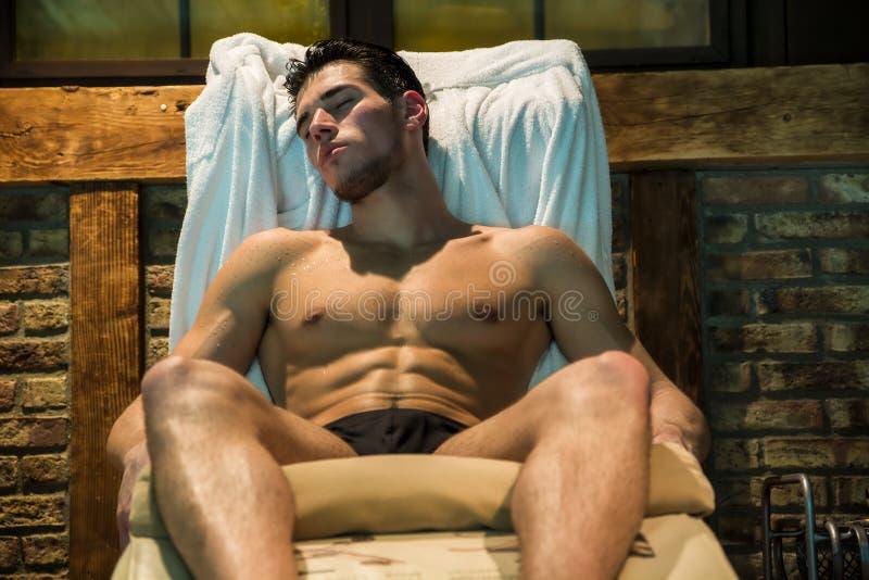 Мышечный человек сидя на шезлонге с глазами закрыл стоковые фотографии rf