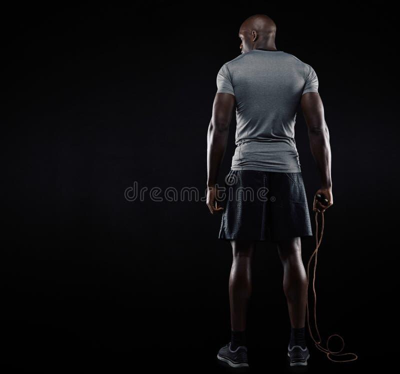 Мышечный человек стоя с скача веревочкой стоковые фотографии rf