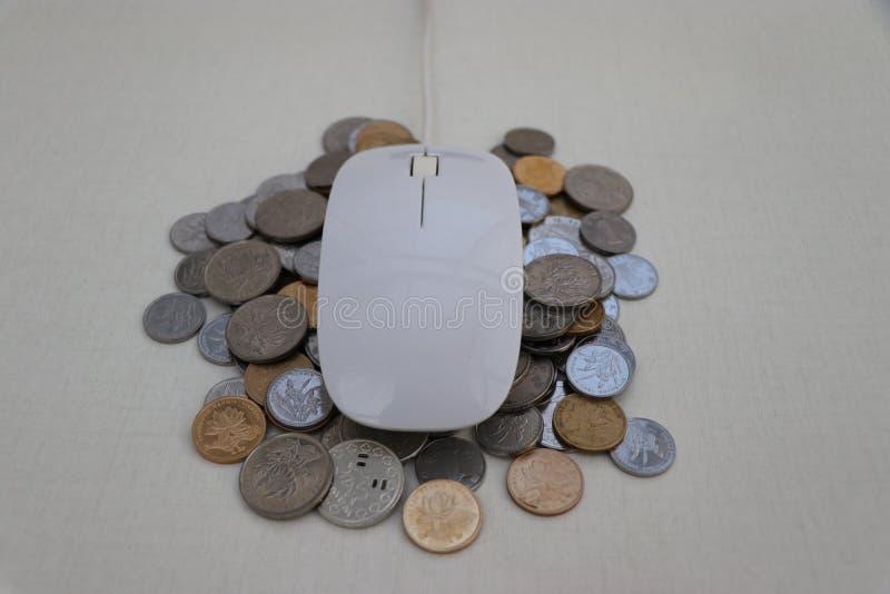 Мышь финансов интернета белая на куче монеток стоковое фото