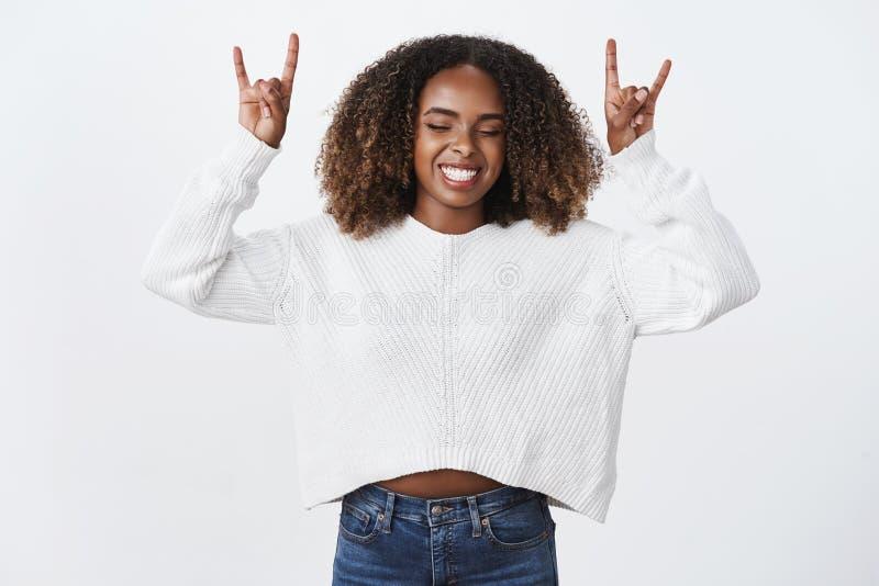 Мы трясем крен n Глаза счастливой беспечальной возбужденной женщины афроамериканца курчавой близкие возбудили жест тяжелого метал стоковые изображения
