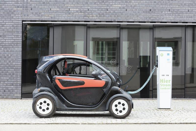Мюнхен, Германия 25-ое июня 2016: Электрический автомобиль, Renault, перезаряжаемый на вставляемой станции перед современным офис стоковые фотографии rf