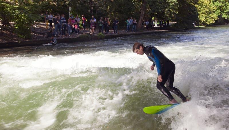 МЮНХЕН, ГЕРМАНИЯ - 1-ОЕ НОЯБРЯ: Серферы тренируют на искусственной волне о 1 метре высокий в реке Eisbach в английском саде стоковое изображение