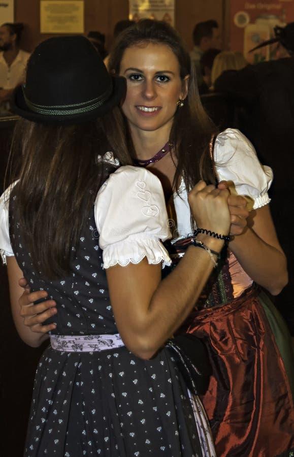 МЮНХЕН, ГЕРМАНИЯ - 18-ОЕ СЕНТЯБРЯ 2016: Oktoberfest Мюнхен: 2 девушки в традиционных костюмах танцуя в павильоне пива стоковое фото