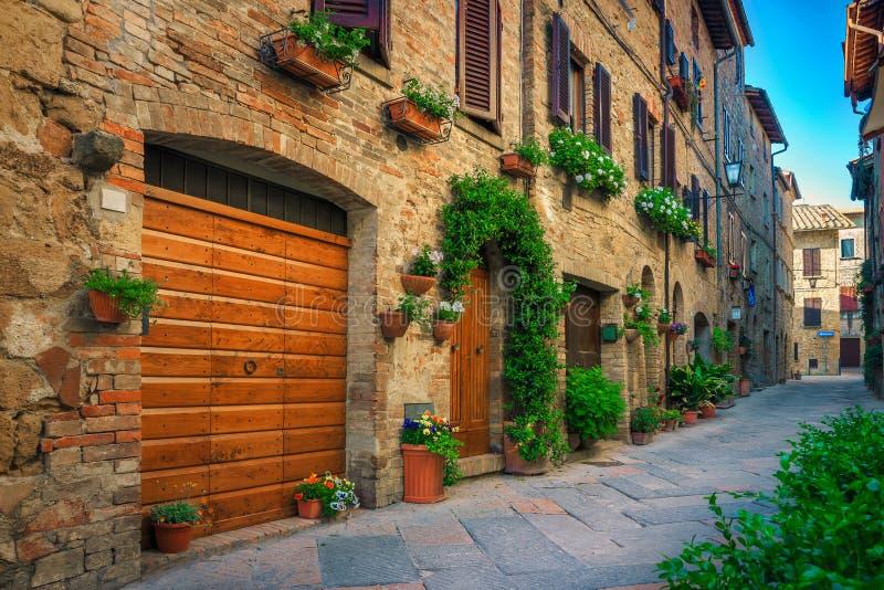 Мягкая узкая улица, украшенная цветами, в Пьенце, Тоскане, Италия стоковая фотография rf