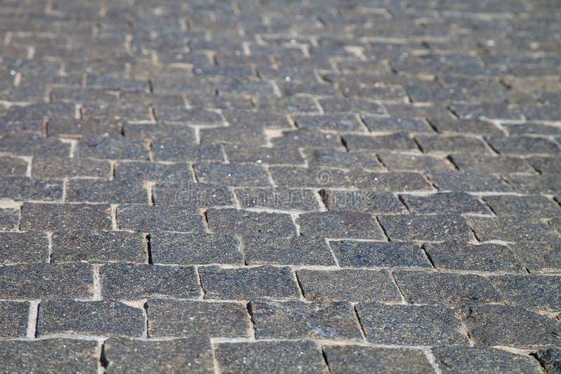 Мягкий конец фокуса вверх по серому backgrou текстуры следа дороги булыжника стоковые фотографии rf