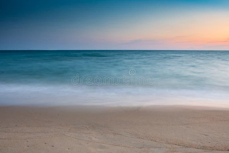 Мягкий пляж волны на море на голубом небе и оранжевом наборе солнца стоковая фотография