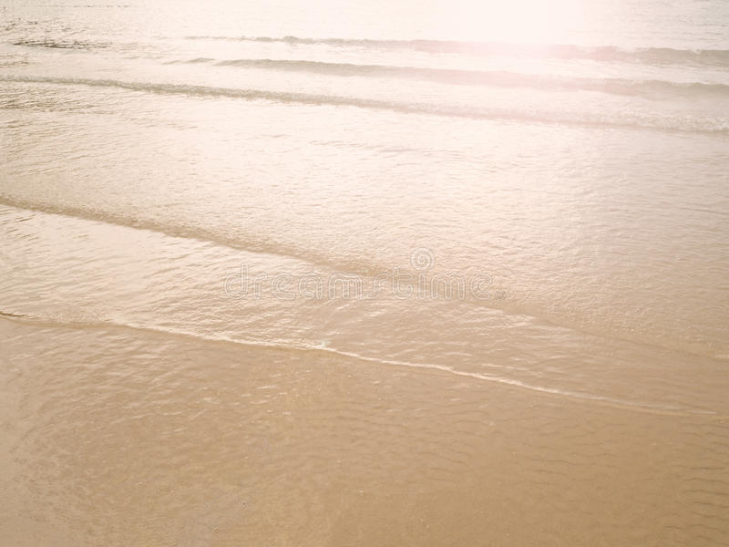 Мягкий пляж песка волны моря на заходе солнца/восходе солнца Оранжевый цвет поверхности морской воды отражает с заходом солнца Ле стоковые изображения rf