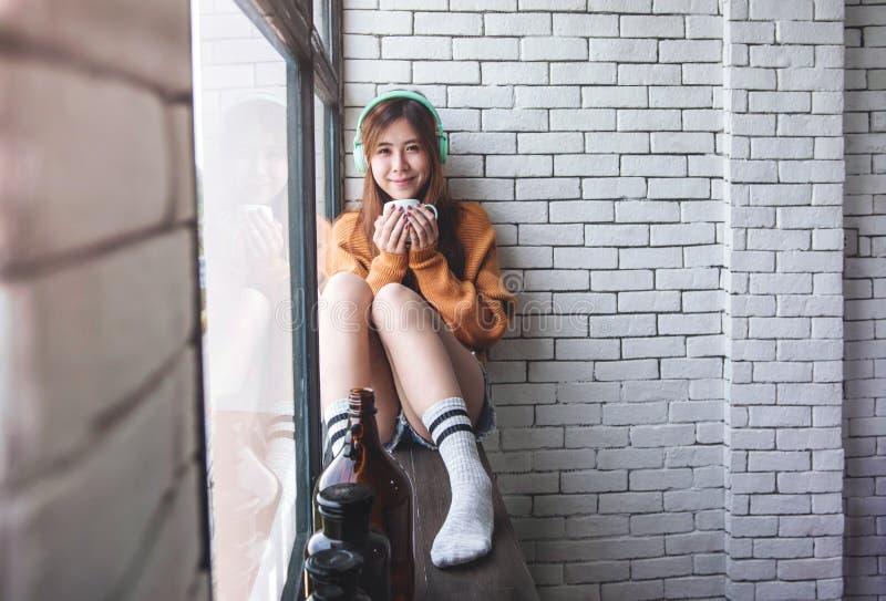 Мягкий фокус молодой женщины ослабляя с музыкой от наушников в окне уютного дома близрасположенном, наслаждаясь с солнечностью ут стоковое фото rf