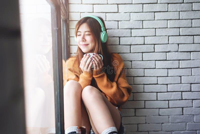 Мягкий фокус молодой женщины ослабляя с музыкой от наушников в окне уютного дома близрасположенном, наслаждаясь с солнечностью ут стоковая фотография
