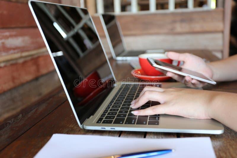 Мягкий фокус молодой женщины фрилансера работая используя ноутбук и руку держа мобильный умный телефон на деревянном столе внутри стоковые фото