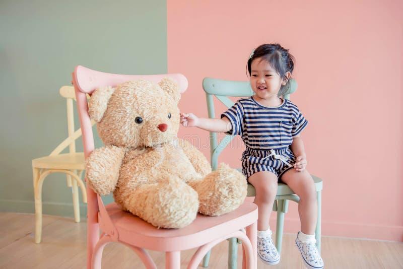 Мягкий фокус ребенка 2 года старого сидя с ее плюшевым медвежонком стоковая фотография rf