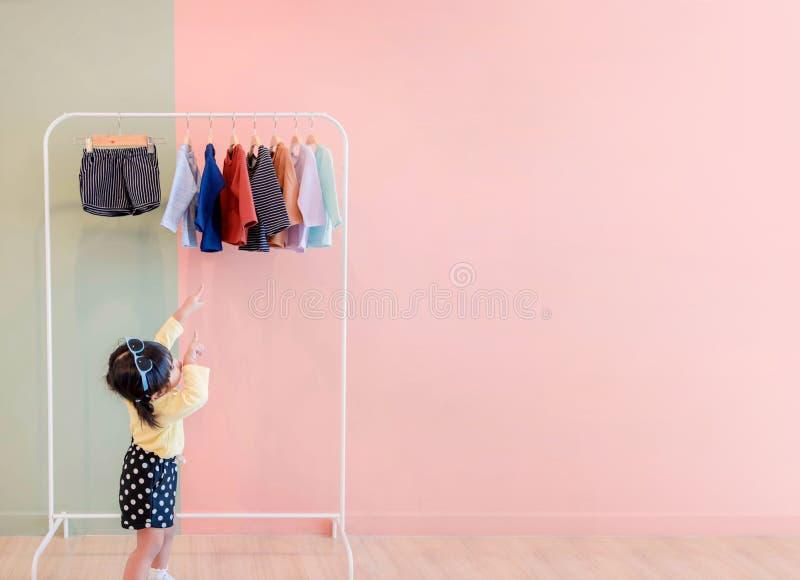 Мягкий фокус счастливых детей указывая ее руки к шкафу ткани для Ch стоковое изображение rf