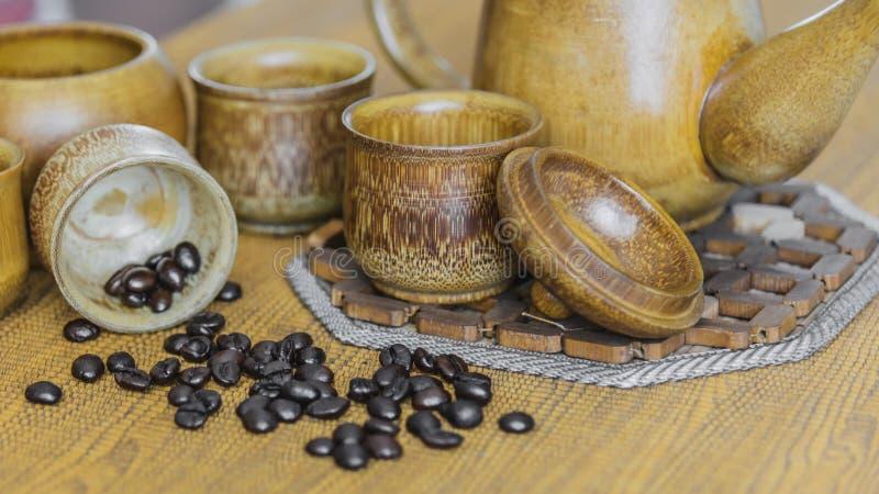 Мягкое изображение фокуса кофейных зерен и кофейных чашек установило на деревянный b стоковая фотография rf
