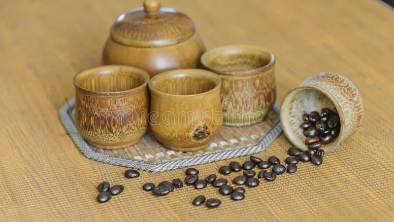 Мягкое изображение фокуса кофейных зерен и кофейных чашек установило на деревянный b стоковые фото