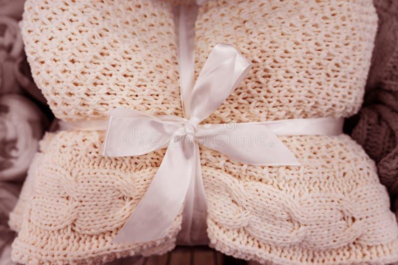 мягкое трикотажное одеяло сложено и завязано белой лентой с носом Понятие комфорта и уюта Подарок на праздники стоковые изображения rf