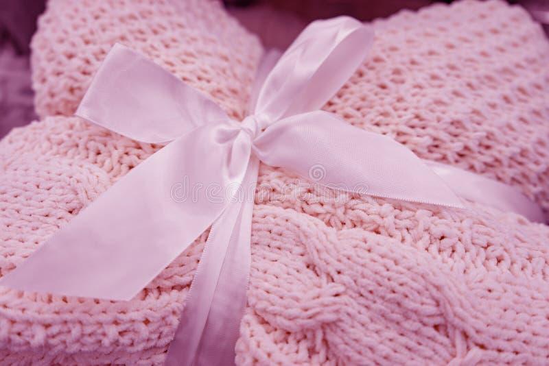 мягкое трикотажное одеяло сложено и завязано белой лентой с носом Понятие комфорта и уюта Подарок на праздники стоковая фотография rf