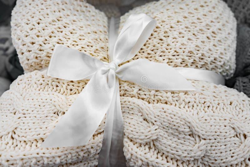 мягкое трикотажное одеяло сложено и завязано белой лентой с носом Понятие комфорта и уюта Подарок на праздники стоковые изображения
