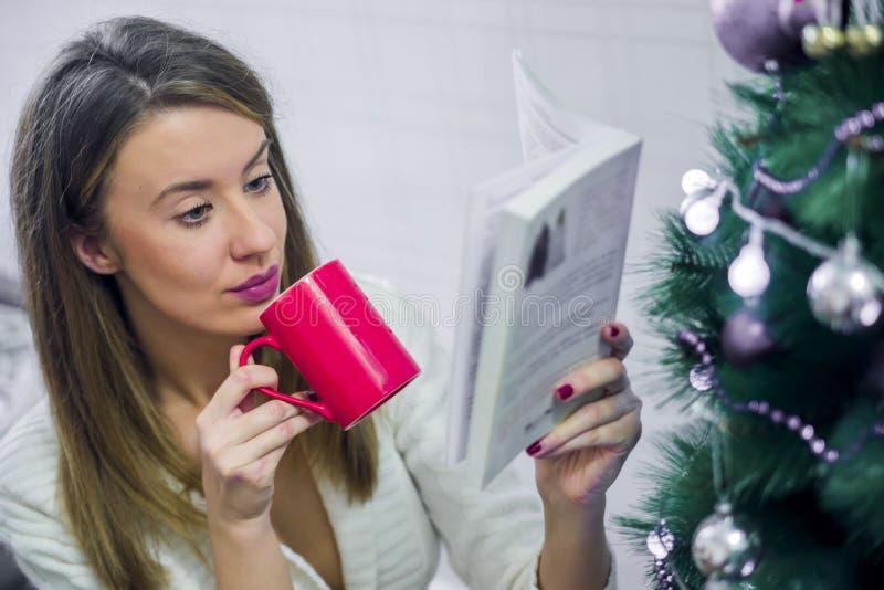 Мягкое фото женщины на кровати с книгой чтения чашки чаю Женщина сидит с чашкой горячих питья и книги стоковое фото